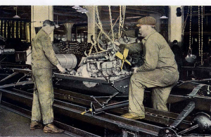 Setting the motor, whilst one worker connects the driveshaft to the engine the other lowers the block and working in choreographed unison they would have the motor installed simultaneously
