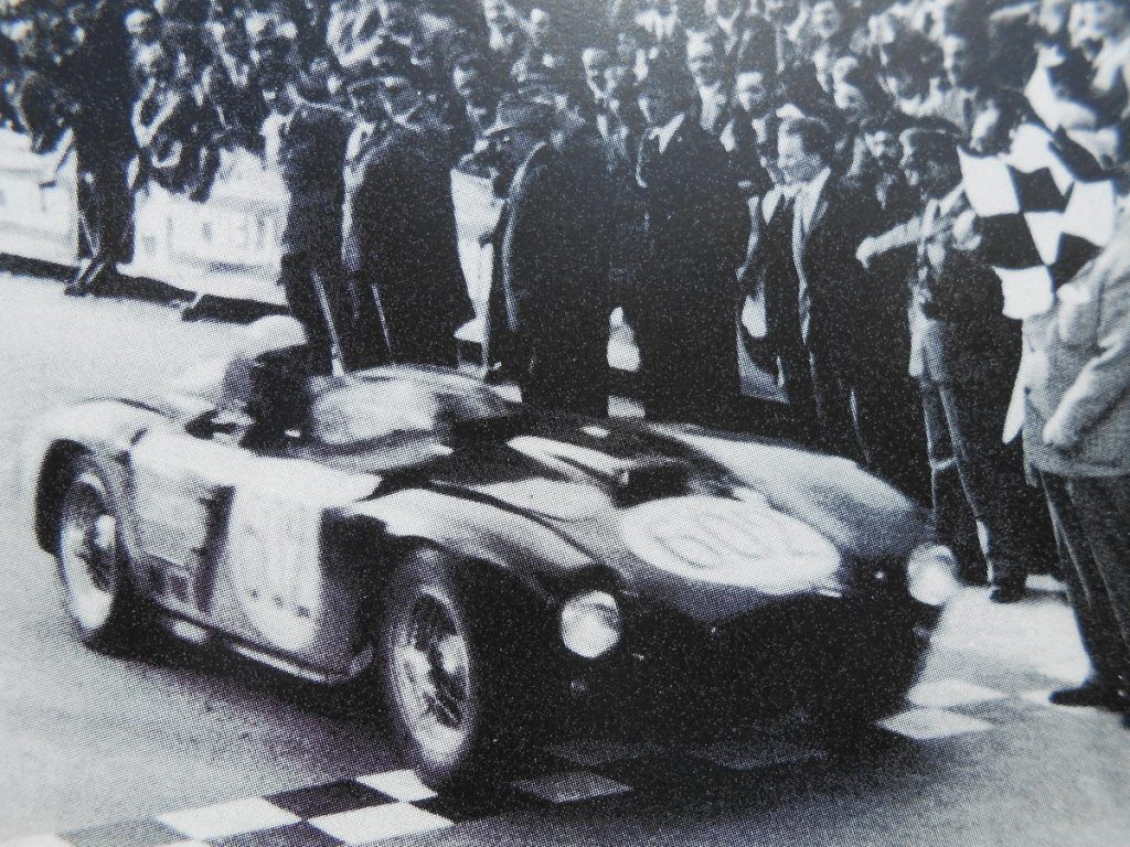 Alberto Ascari blasts across the finish line to take victory in the 1954 Mille Miglia piloting Lancia's D24